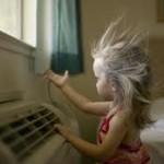 Маленькая девочка возле работающего напольного кондиционера, волосы развивает ветром
