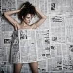 Девушка приклеенная газетами к стене