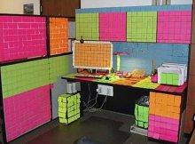 Стикеры наклеены на стену, перегородку, рабочий стол, компьютер и монитор
