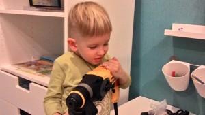 Маленький мальчик держит в руках жёлтый перфоратор
