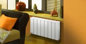 Маленький алюминиевый радиатор отопления под окном