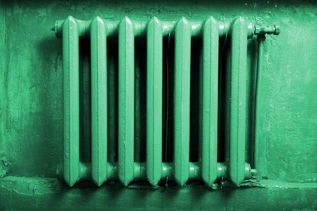 Старая чугунная батарея отопления зелёного цвета